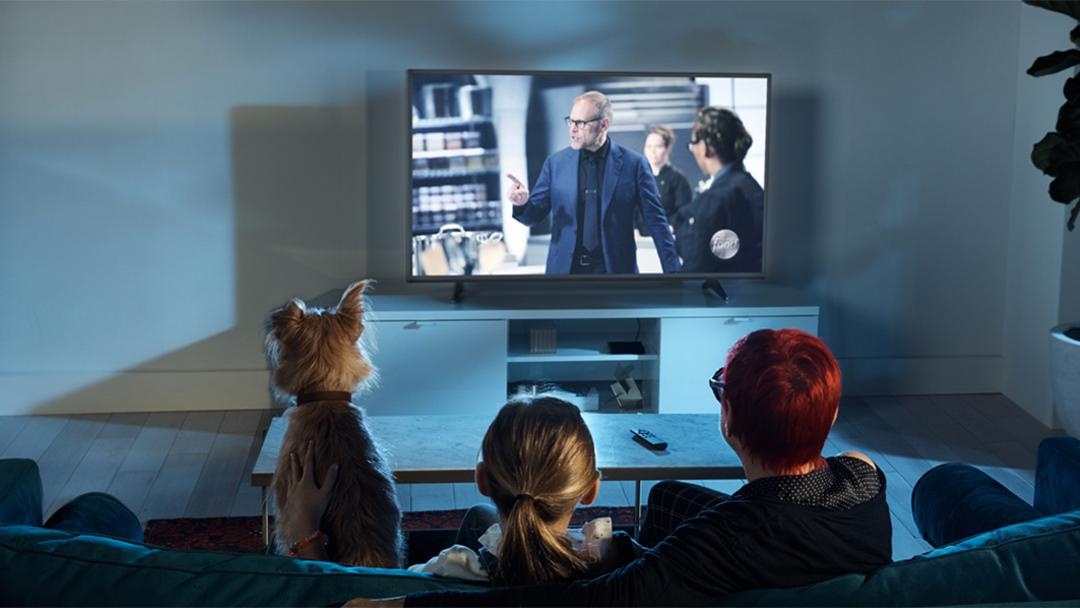 Una familia sentada alrededor de una Amazon Fire TV