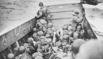 Los soldados se agachan detrás de los baluartes de una barcaza de desembarco de la Guardia Costera en su camino a Normandía.